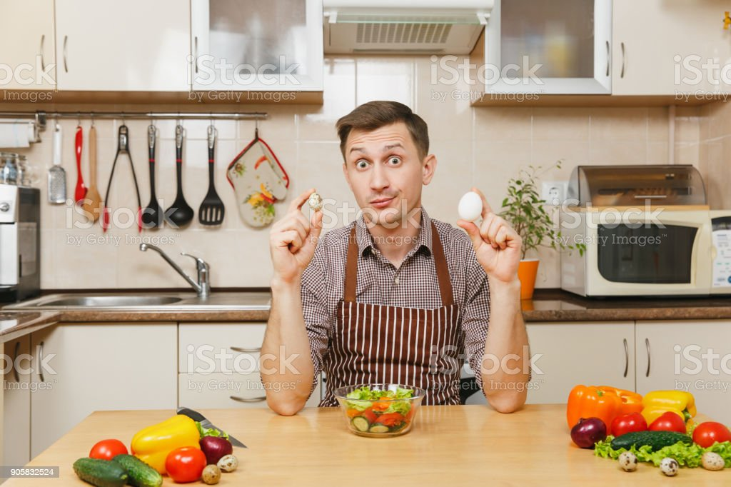 Handsome caucasian young man in apron, brown shirt sitting at table, holding chicken and quail eggs, vegetable salad in light kitchen. Dieting concept. Healthy lifestyle. Cooking at home. Prepare food stock photo