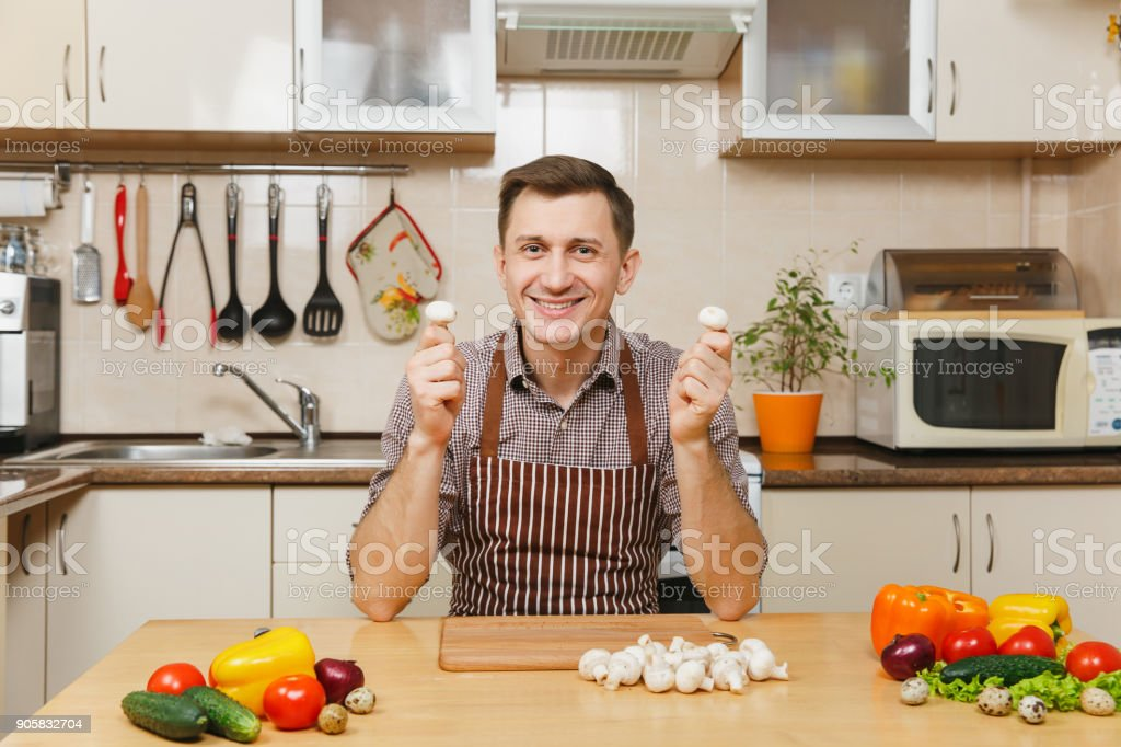 Handsome caucasian young man in apron, brown shirt sitting at table with vegetable, cutting champignon mushrooms in light kitchen. Dieting concept. Healthy lifestyle. Cooking at home. Prepare food. stock photo