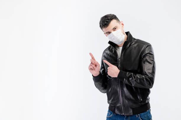 Hübscher kaukasischer junger Mann in schwarzer Jacke und blauer Jeans mit Einweg-Gesichtsmaske. Schutz vor Viren und Infektionen. Studioportrait, Konzept mit weißem Hintergrund. Er gestikuliert, kopiert Platz für Ihr Design. – Foto