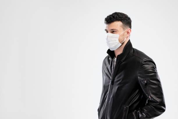 Schöne kaukasische junge Mann in schwarzer Jacke mit Einweg-Gesichtsmaske. Schutz vor Viren und Infektionen. Studioportrait, Konzept mit weißem Hintergrund. Kopieren Sie Speicherplatz für Ihr Design. – Foto