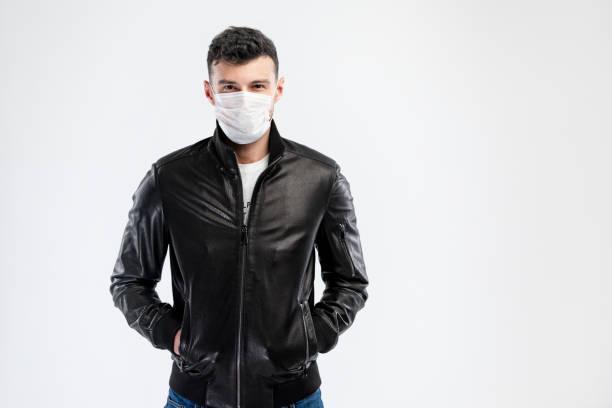 Schöne kaukasische junge Mann in schwarzer Jacke mit Einweg-Gesichtsmaske. Schutz vor Viren und Infektionen. Kopieren Sie Speicherplatz für Ihr Design. – Foto