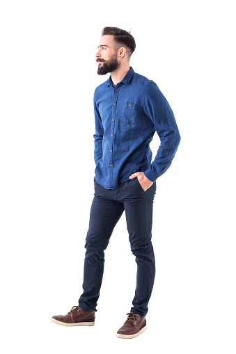 931173966 istock photo Handsome charming bearded business casual man with hands in pockets looking away and smile 931178760