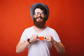 istock Handsome cheerful bearded guy, wearing a hat, holding a little paper heart over chest, red isolated background 1163516864