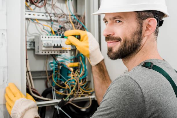 electricista alegre guapo reparar caja eléctrica y con destornillador en corredor - electricity fotografías e imágenes de stock