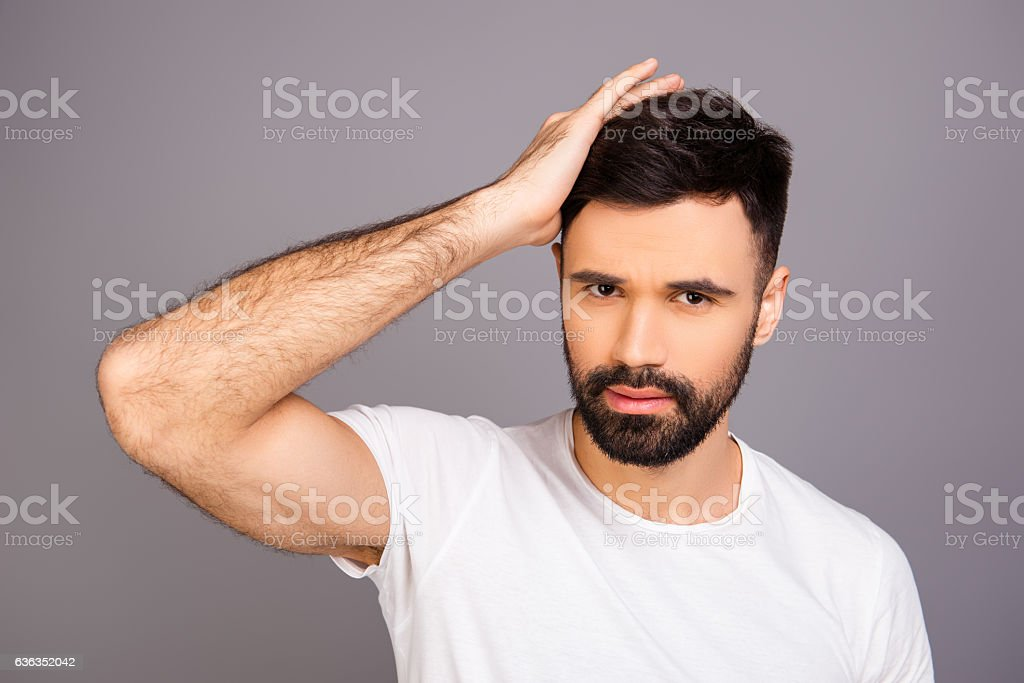 Handsome cheerful young man combing his hair with fingers stock photo