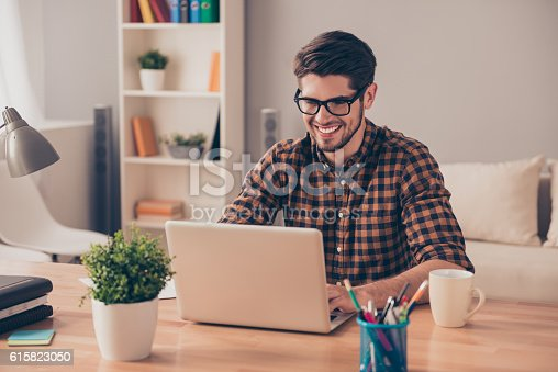 Handsome cheerful young man in glasses typing on laptop