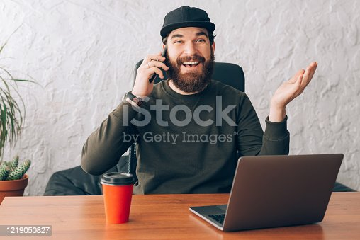 Photo of handsome cheerful young man talking on smartphone while sitting in office