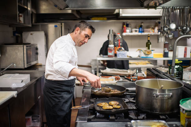 Hübscher Chef-Koch in Uniform, Kochen auf dem Gasherd in der Küche – Foto