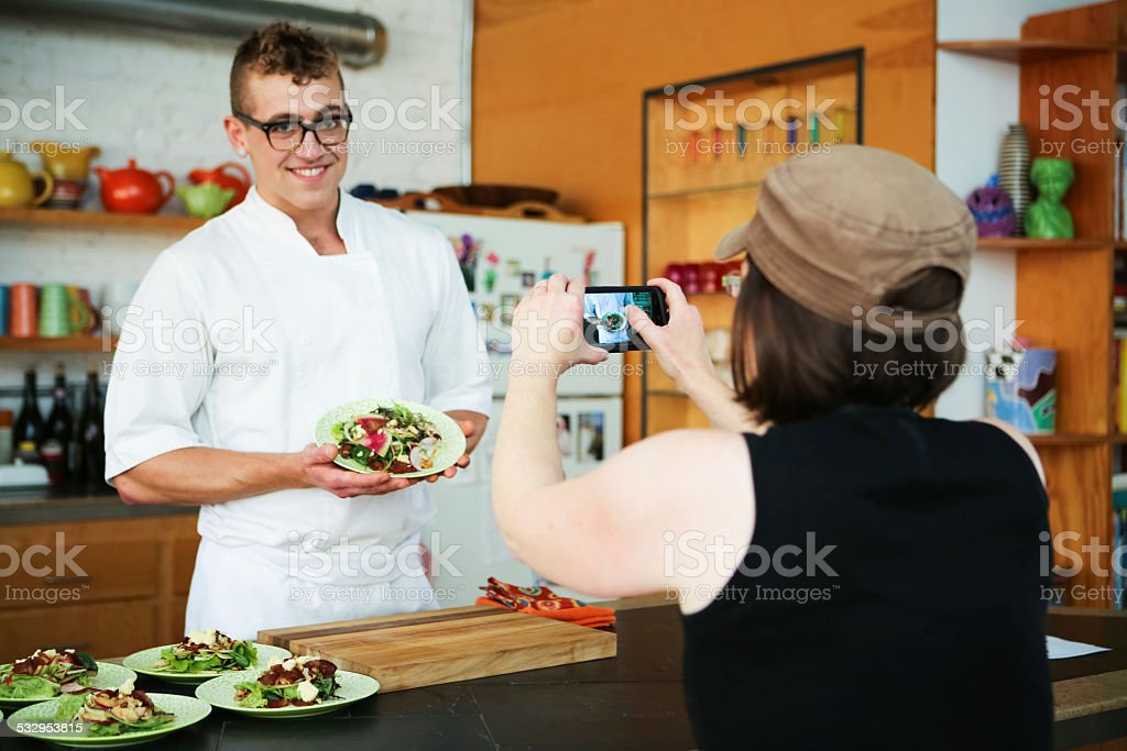 Handsome Chef Cooking in Modern Kitchen Poses for Smartphone Photograph stock photo