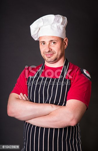 istock Handsome chef posing against black background 610423928