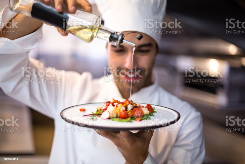 Handsome chef pouring olive oil on meal stock photo