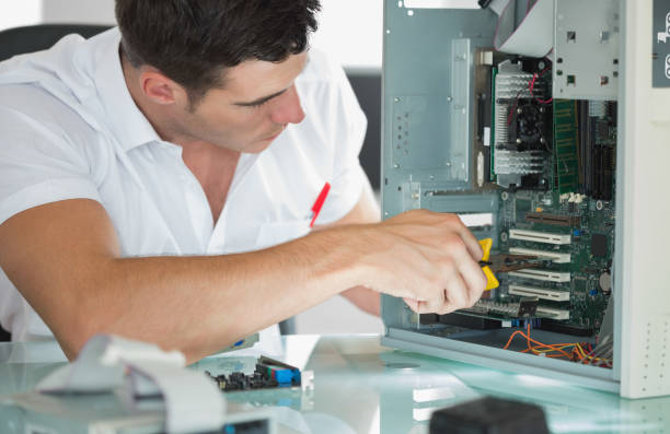 Handsome computer engineer repairing computer with pliers stock photo