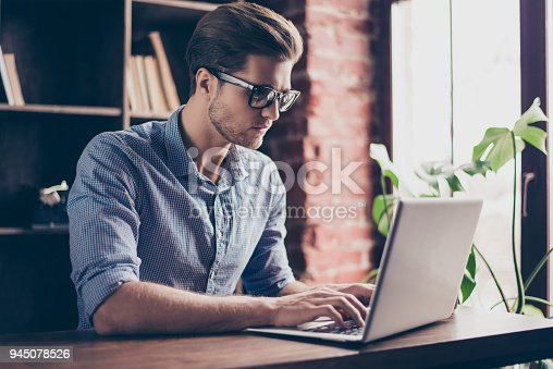 istock Handsome concentrated young man in glasses typing on laptop 945078526