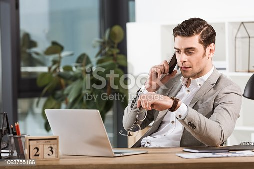 handsome confident businessman talking by phone at workplace in office