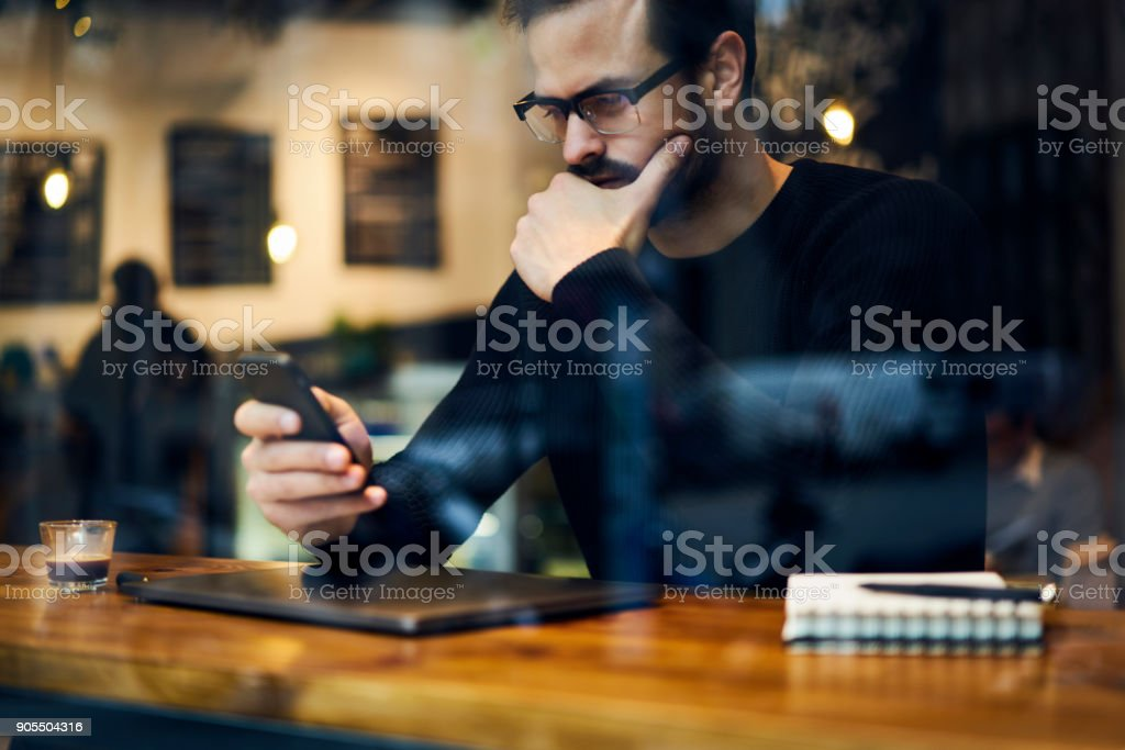Handsome confident male journalist monitoring latest news on informational websites choosing events and themes to create publication chatting with colleagues and editor via smartphone and wifi stock photo