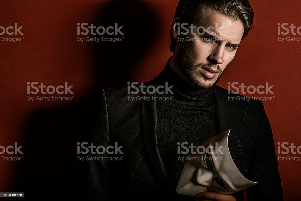 handsome confident man holding a mask stock photo