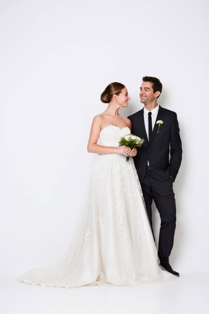 Handsome couple The handsome newlywed couple standing in white studio bridegroom stock pictures, royalty-free photos & images