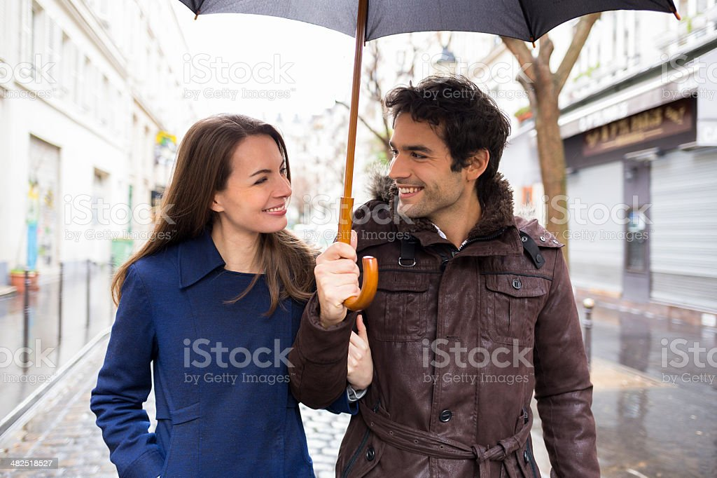Handsome couple under the rain on street stock photo