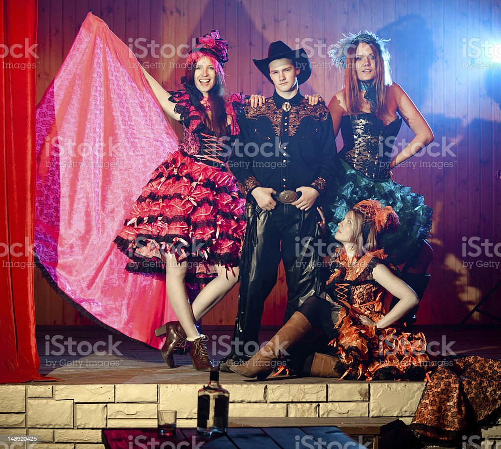 Handsome cowboy and tree cancan dancers stock photo
