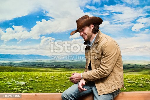 Handsome cowboy wearing denim jacket and jeans and cowboy hat