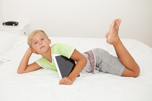 Handsome Cute Blond Boy Lying On The Bed With Tablet Stock ...