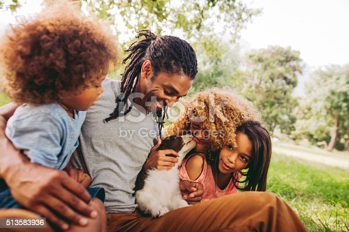 518064982 istock photo Handsome dad laughs as his beautiful wife gets puppy kisses. 513583936