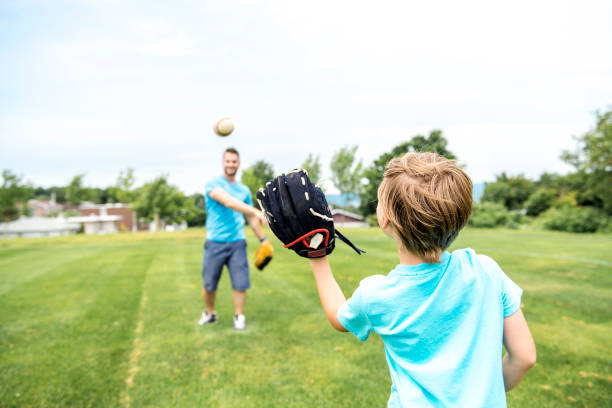 Handsome dad with his little cute sun are playing baseball on green grassy lawn A Handsome dad with his little cute sun are playing baseball on green grassy lawn baseball sport stock pictures, royalty-free photos & images