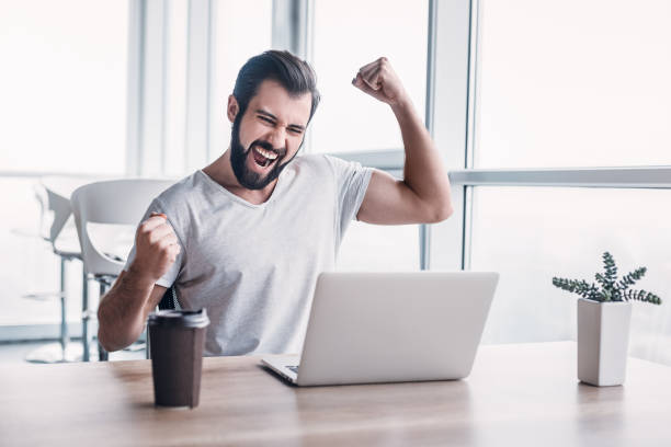 Handsome dark-haired businessman celebrating success with arms raised while looking at his laptop screen. In the office businessman sitting at the desk, using laptop finishes project and wins big. Makes successful gestures, raises arms in celebration. His cup of coffee is in front of him yeah right stock pictures, royalty-free photos & images