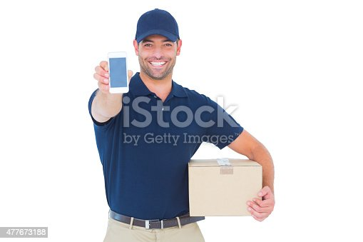 istock Handsome delivery man showing mobile phone 477673188