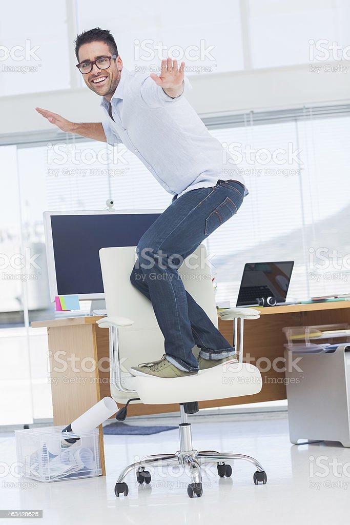 Handsome designer surfing his swivel chair stock photo
