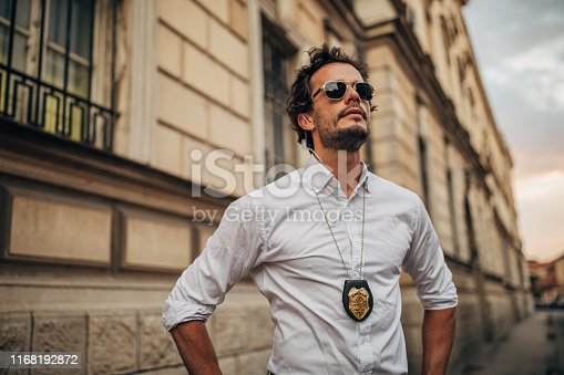 One man, handsome young detective with police badge around neck, standing on the street.