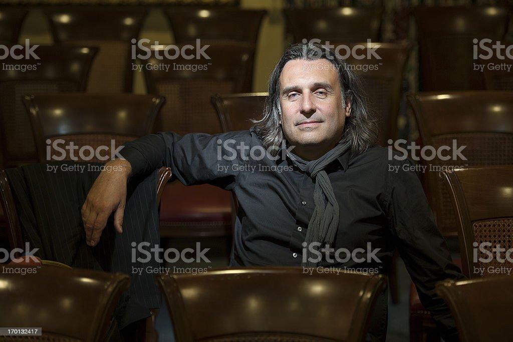 Handsome director is sitting in empty auditorium stock photo