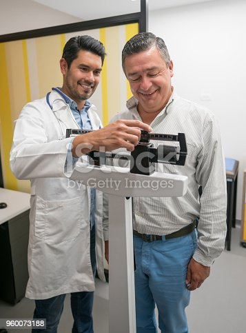 Handsome doctor checking the weight of a mid adult male patient both smiling very happy