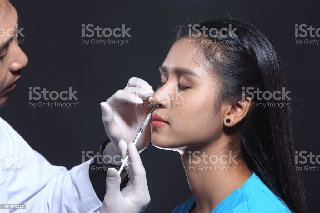 Handsome Doctor inject beauty chemical to cheek, chin, nose, eyebrow, forehead by syringe needle to beautiful patient woman royalty-free stock photo