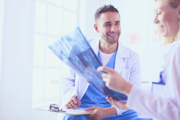 Hübsche Ärztin spricht mit jungen Ärztin und macht sich Notizen, während er in seinem Büro sitzt. – Foto