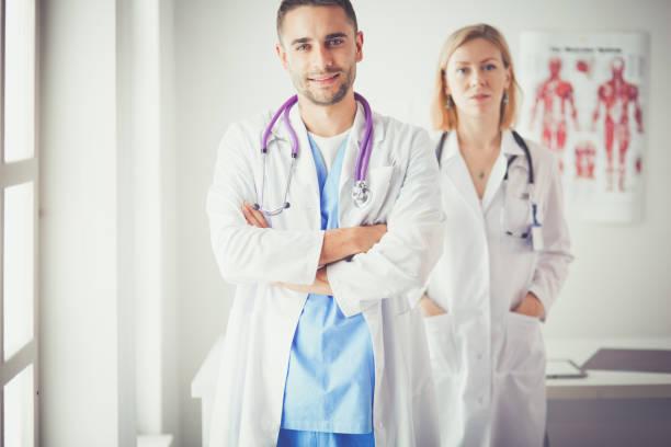 Hübscher Arzt im Gespräch mit jungen Patientin und Notizen beim Sitzen in seinem Büro – Foto