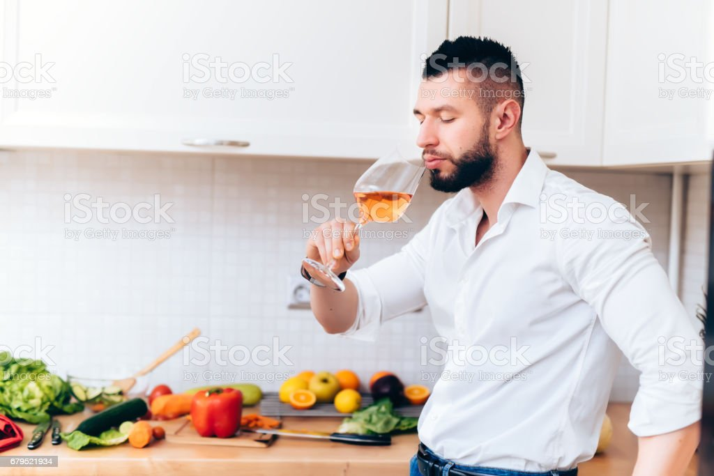 Handsome elegant man drinking a glass of rose wine during dinner preparation. Modern cook sipping from wine while cooking salad royalty-free stock photo