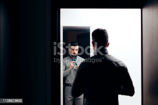 istock Handsome Elegant Man Looking in the Mirror 1128623800
