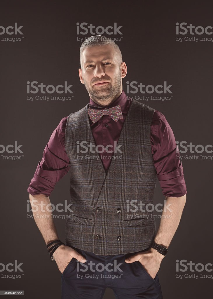 Handsome elegant man wearing bow tie and tweed vest Fashionable elegant man wearing tweed vest, shirt and bow tie, looking at camera. Dark tone, black background. 2015 Stock Photo