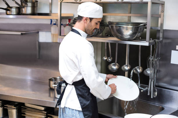 Handsome employee doing dishes Handsome employee doing dishes in commercial kitchen dishwasher stock pictures, royalty-free photos & images