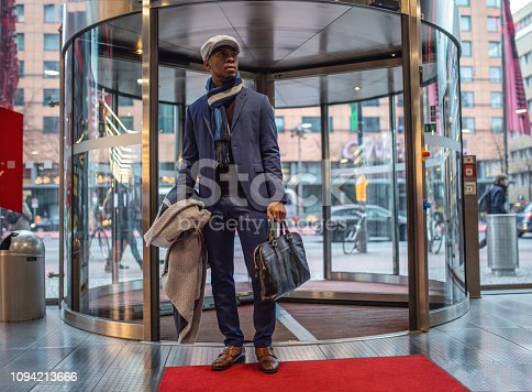 Handsome and beautiful black businessman entering the mall through rotating doors.