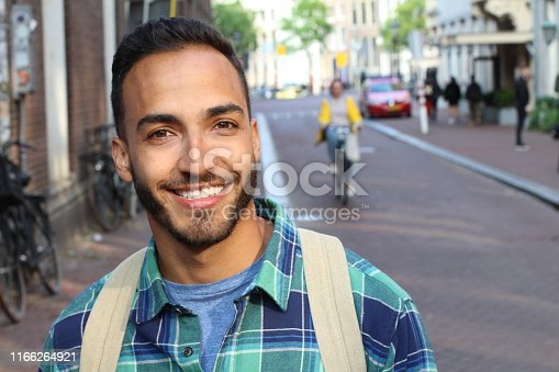 Handsome ethnic young male smiling outdoors.