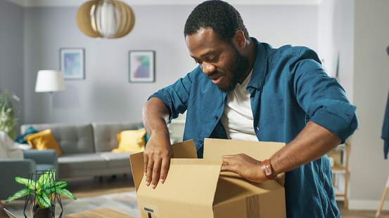 istock Handsome Excited Man Opens Cardboard Box Postal Package and Is Very Happy with Content. Man Package Unboxing. 1059208880