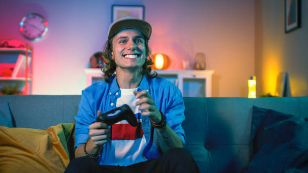 handsome excited young gamer with long hair and a cap is sitting on a couch and playing video games on a console. he plays with a wireless controller. cozy room is lit with warm and neon light. - man joystick imagens e fotografias de stock