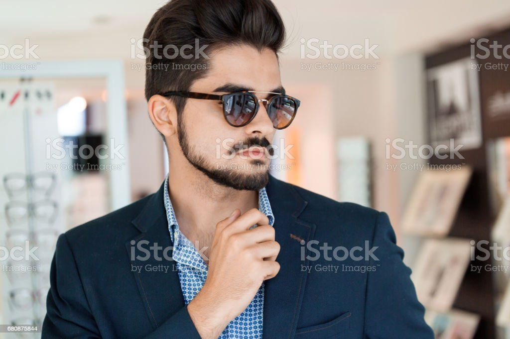 Handsome fashion young man posing in new sunglasses royalty-free stock photo