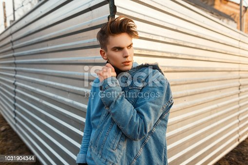 846124694istockphoto Handsome fashionable guy with a hairstyle in a denim shirt and a stylish jeans jacket posing near a metal wall 1031904344
