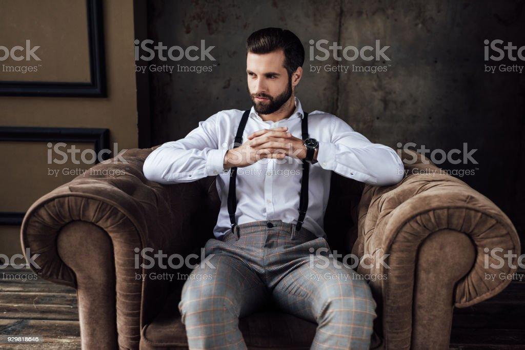 bel homme à la mode, pensée et assis dans le fauteuil - Photo