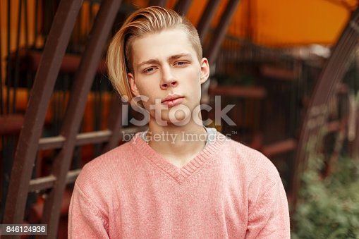 846124694 istock photo Handsome fashionable young man in a pink sweater in the park 846124936