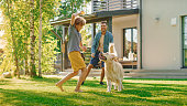istock Handsome Father, and Son Play Catch With Loyal Family Friend Golden Retriever Dog. Family Spending Time Together Training Dog. Sunny Day Idyllic Suburban Home Backyard. 1285465119