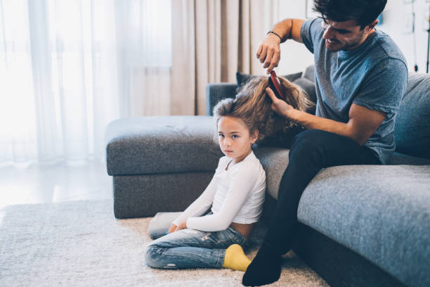 Handsome father brushing hair of daughter Handsome father brushing hair of little cute daughter at home stay at home father stock pictures, royalty-free photos & images